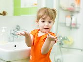 Funny little girl washing hands in bathroom