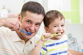 father and child brushing teeth in bathroom