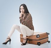 Asian woman thinking and sitting on a luggage in vintage style.