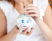 Primer plano de una mujer de ahorrar dinero en una alcancía