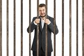 crying businessman behind the prison cell over white background