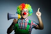 Clown with loudspealer against curtain
