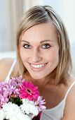 image of beautiful young woman  - Portrait of a happy woman holding a bunch of flowers at home - JPG