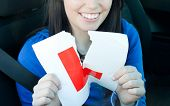 Charming Teen Girl Sitting In Her Car Tearing A L-sign