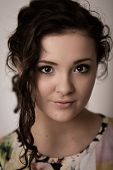 Portrait Of A Beautiful Girl With Brown Eyes Against A Grey Back Ground