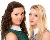 Portrait Of Two Beautiful Teenage Sister Girls With Brown Eyes Against A White Background