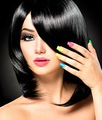 Beautiful Brunette Girl with Healthy Black Hair, haircut. Colorful manicured nails Isolated on Black background. Beauty Woman with Short Black Hair