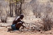 Himba Man Adjusts Wooden Souvenirs In Fireplace For Tourists