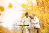 picture of romantic  - Active senior couple together enjoying romantic walk with bicycle in golden autumn park - JPG