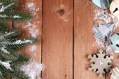 Green fir tree with toys and snow on wooden background