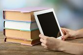 Female hand holding PC tablet near books, close-up. Modern  education concept