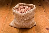 image of phaseolus  - Loose dry pinto beans in burlap sack on wooden board background - JPG