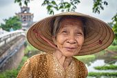 HUE, VIETNAM - APRIL 3, 2014: Unidentified Vietnamese woman wearing traditional conical hat poses for the camera in Hue, Vietnam on April 3, 2014.