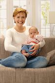 Happy young mother holding baby girl in arms, smiling, sitting on sofa.