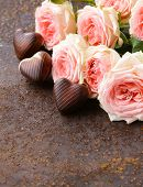 chocolate candy in the shape of hearts and pink roses for Valentine's day holiday