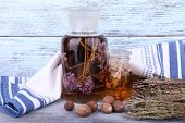 Bottles of herbal tincture and dried leaves on wooden background