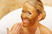Portrait of a happy woman showing her face with chocolate mask.