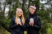 Happy young couple in love wearing Santa hats and holding big snowflakes. Man and woman celebrating