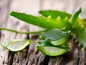 stock photo of aloe-vera  - Aloe Vera leaves on wooden background - JPG