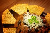 Mexican food: chili with meat served with nachos on wooden background