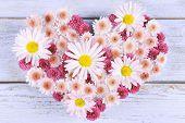 Beautiful flowers in heart shape on wooden background
