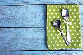 Metal spoons on green polka dot napkin on wooden background