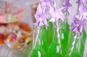 Bottles of drink with straw and sweets on table close up