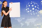 Beautiful businesswoman in dress holding empty paper sheet. World map, graphs and texts as backdrop