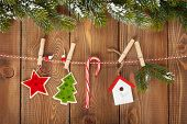 Snow fir tree and christmas decor on rope over rustic wooden board