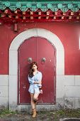 Asian Woman Standing By Red Chinese Door