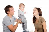 Joyful mother and father playing with his little son. Child seven months.