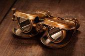 Vintage opera glasses binoculars on old wooden background
