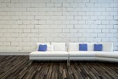 3D Rendering of White Couch with White and Blue Pillows on an Architectural Living Room with Seamless Concrete Wall and Wooden Flooring Design