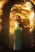 Beautiful blonde with a long curly hair in a long evening dress in static outdoors near retro vintag