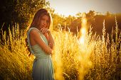 Beautiful blonde with a long curly hair in a long evening dress in motion outdoors in nature in summ