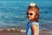 Happy Kid Girl In Sun Glasses On Blue Sea Background