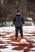 serious boy standing in front of ball