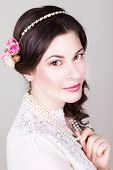 Beautiful brunette bride smiling with natural make up and flowers roses in her hairstyle