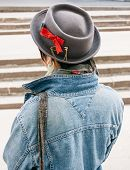 Close up Rear View of Fashionable Woman Wearing Stylish Hat with Red Ribbon and Denim Jacket. Captured Outdoor.