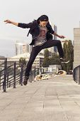 Young Blonde Guy Jumping On Skateboard In Casual Outfit In The Urban City Outdoors. Active. Sport
