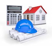 Small model house with red roof near scrolls of architectural drawings and calculator