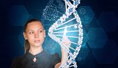 Beautiful businesswoman in dress presses finger on model of DNA