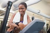 Fit woman working out on the cross trainer at the gym