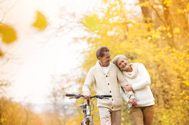 stock photo of retirement age  - Active senior couple together enjoying romantic walk with bicycle in golden autumn park - JPG