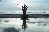pic of  practices  - Silhouette young woman practicing yoga on the beach - JPG