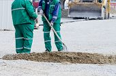 foto of shovel  - Two workers with shovel working on street construction site bulldozer in background - JPG
