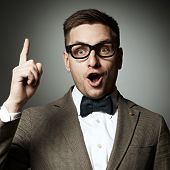 picture of nerd  - Confident nerd in eyeglasses and bow tie against grey background - JPG