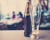 stock photo of tumbler  - beer bottle and empty glass on the background of the bar - JPG