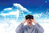 stock photo of binoculars  - Suprised businessman looking through binoculars against bright blue sky with clouds - JPG