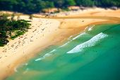 image of tilt  - Tropical sandy beach landscape from high view point tilt shift effect. Beautiful turquoise ocean and people relaxing in waives. Rawai Ya Nui beach Phuket Thailand ** Note: Soft Focus at 100%, best at smaller sizes - JPG